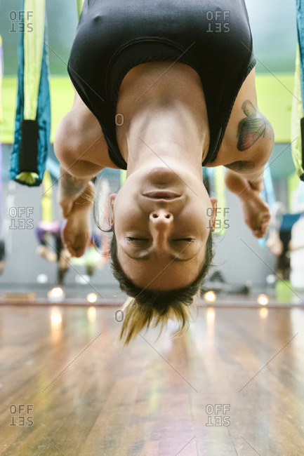 Woman practicing aerial yoga in class