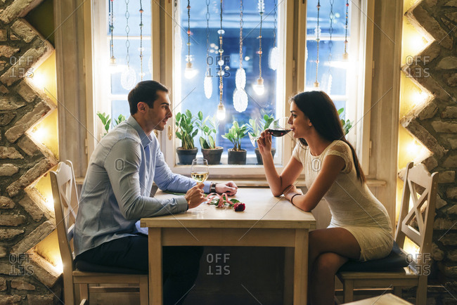 Young couple drinking wine in a restaurant at Valentine's Day