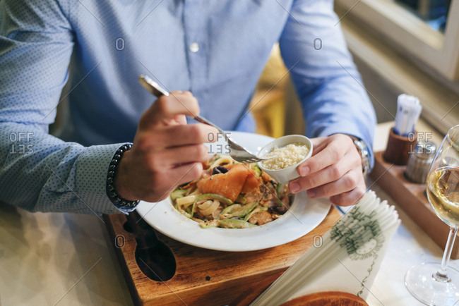 Man having dinner in a restaurant- partial view