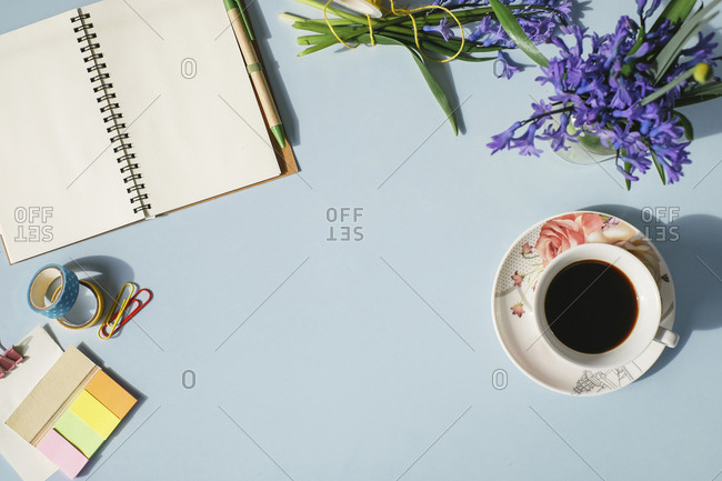 Notebook- office supplies- cup of coffee and spring flowers on light blue background