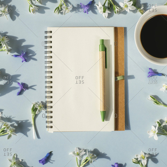 Notebook- pen- cup of coffee and spring flowers on light blue background