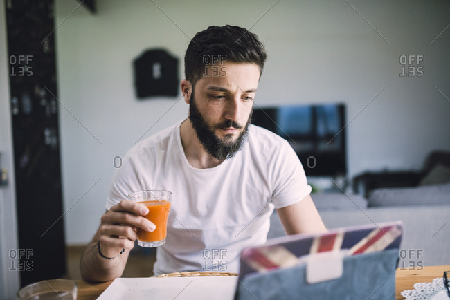 Young man having breakfast - Offset