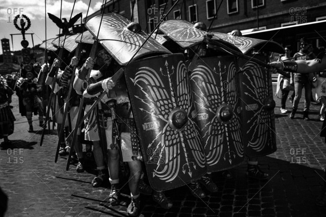 Rome, Italy - April 23, 2017: A group of men dressed as an army of Roman soldiers carrying shields and spears