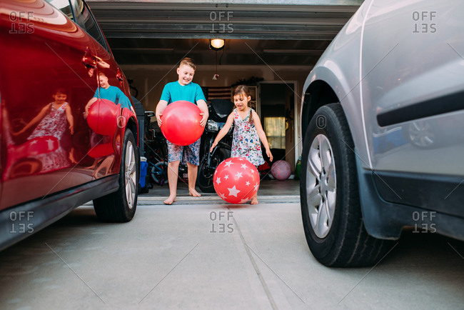 Boy and girl playing together with large bouncing balls in the driveway