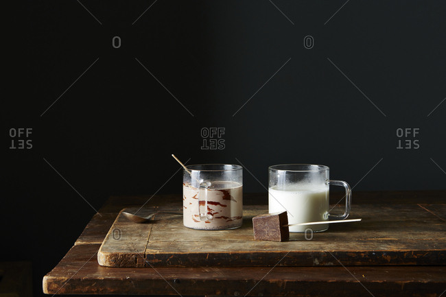 Hot chocolate on a stick being stirred into hot milk
