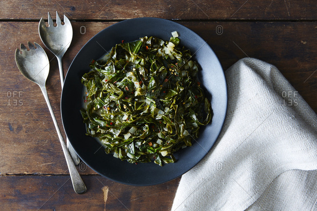 Plate of collard greens with serving utensils