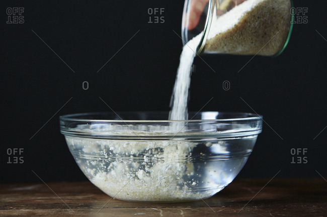 Pouring grits into bowl of water