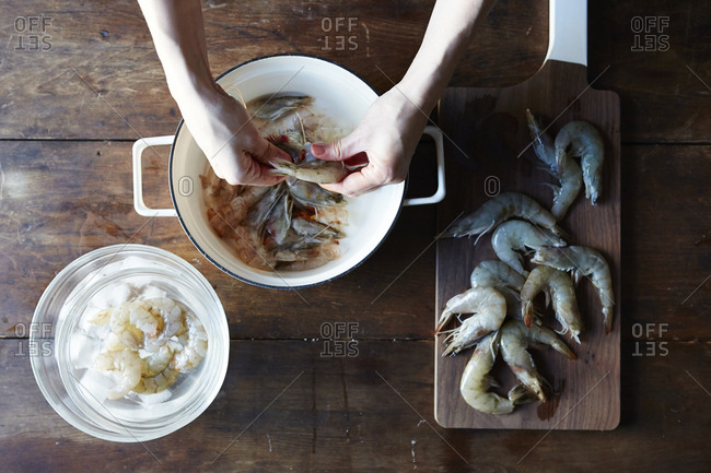 Overhead view of person shelling fresh shrimp
