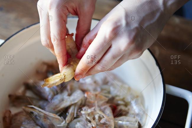 Hands peeling fresh shrimp - Offset