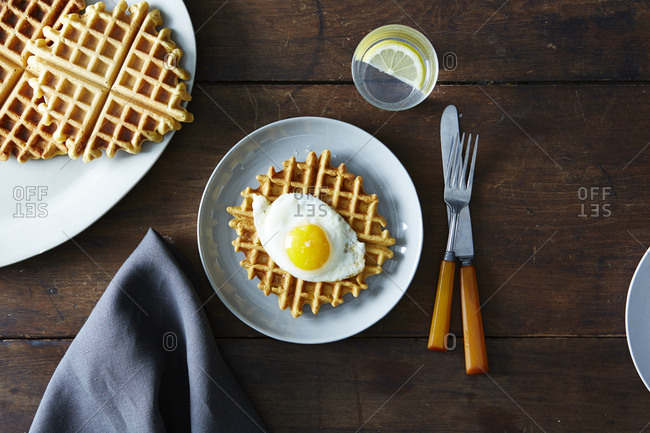 Fresh waffle topped with a fried egg