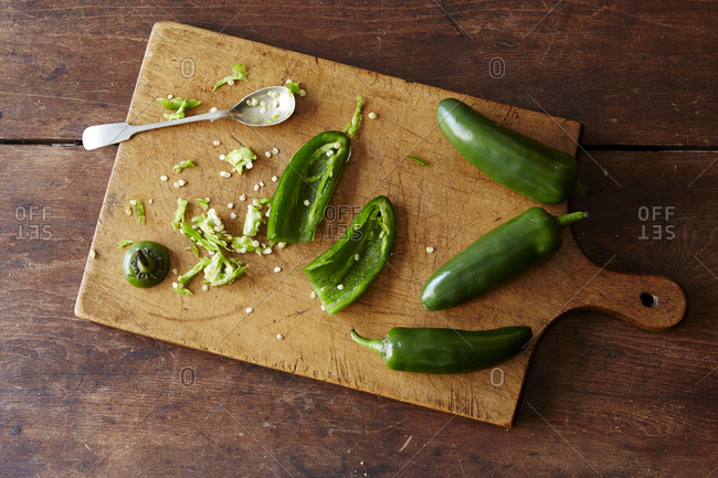 Wooden cutting board with de-seeded jalapeno pepper