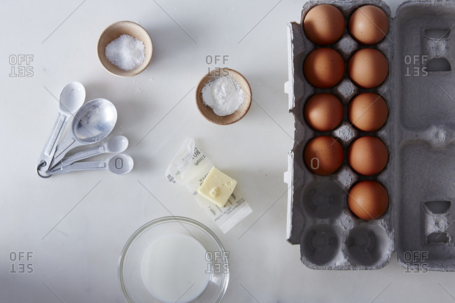 Overhead view of carton of eggs with butter, milk and salt