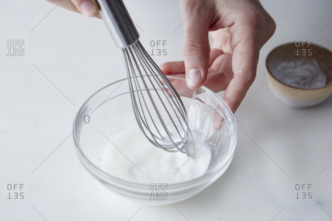 Person whisking dish of milk