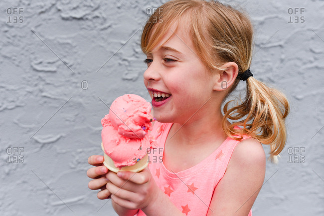 Happy young girl in pigtails with ice cream cone