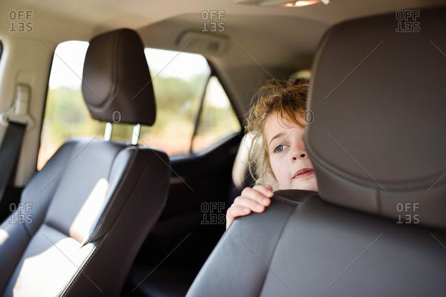 Young girl peeking around seat of car