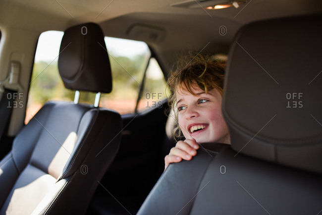 Smiling young girl in back seat of car