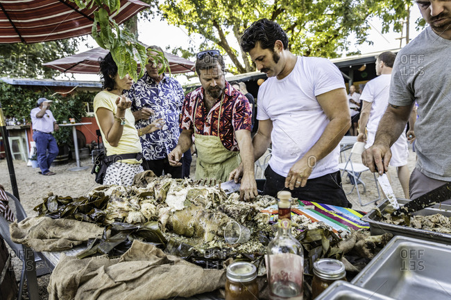Healdsburg, California - January 8, 2015: A crowd of onlookers anxiously await their turn to dig into their meal of the banana wrapped roast pig buried for 8 hours and cooked in the ground