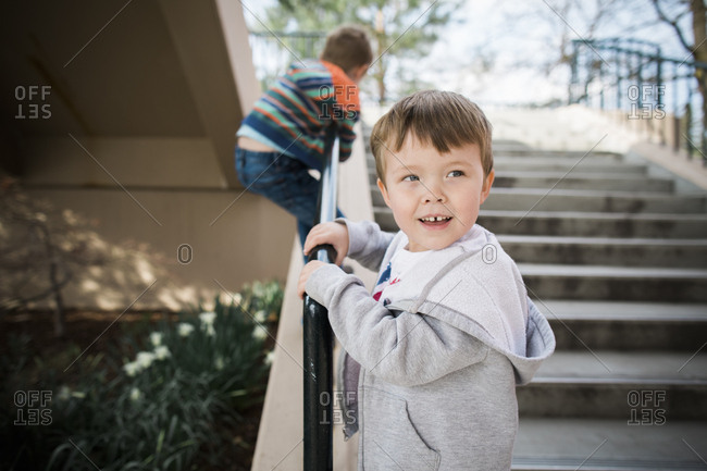 Brothers climbing on the railing of a building's exterior steps