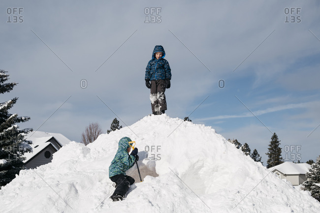 Little boys playing outside on a large pile of snow
