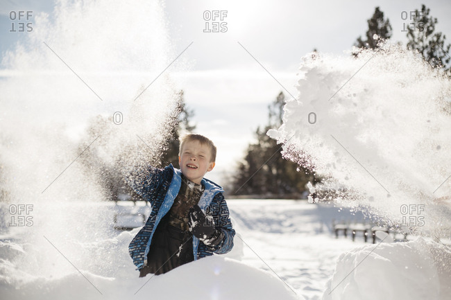 Little boy throwing snow into the air while playing outside