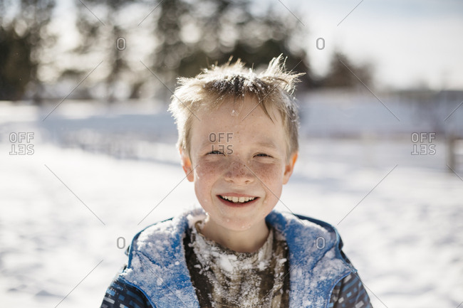 Little boy playing outside covered in snow