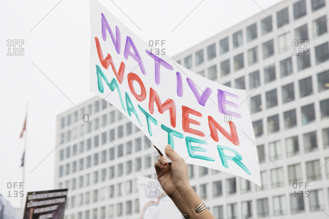 "Hand of a woman holding a sign saying ""Native Women Matter"""