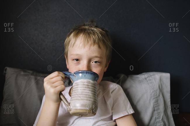Sick little boy sitting in bed drinking a mug of hot tea