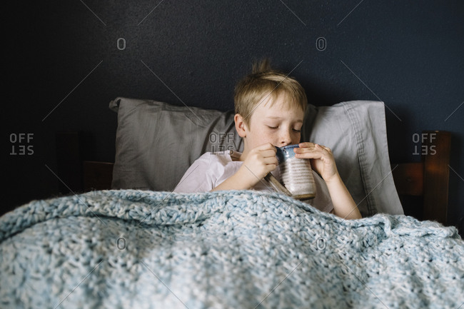 Little boy lying in bed sipping a mug of tea