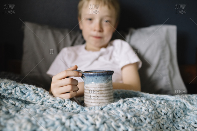 Sick little boy holding a mug of hot tea in bed