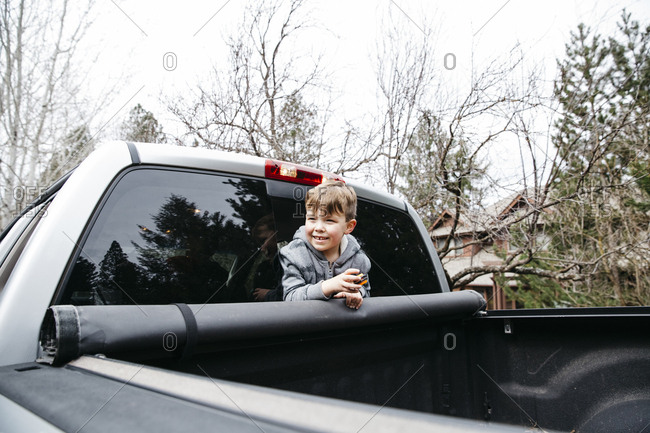 Little boy poking his head from the back window of a truck cab