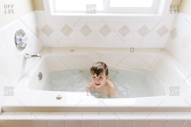 Little boy playing in a bathtub