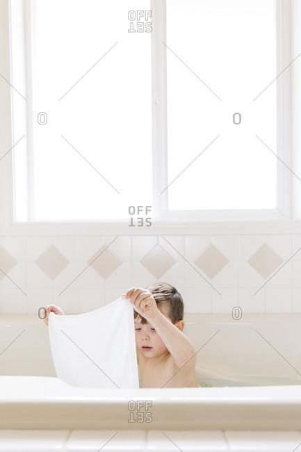 Little boy sitting in a bathtub holding up a washcloth