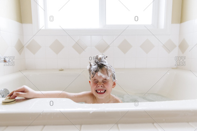 Boy with shampoo in his hair making a silly face in a tub