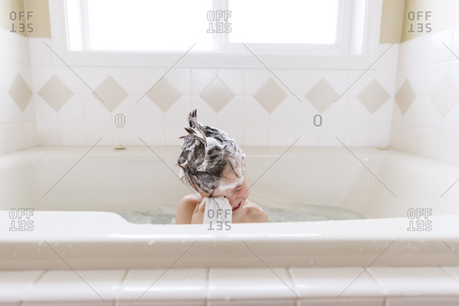 Boy in a tub with shampoo in his hair wiping his face
