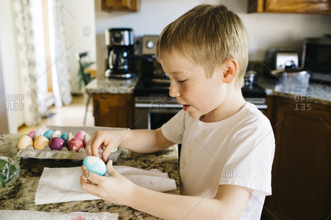 Little boy in a kitchen holding a dyed Easter egg