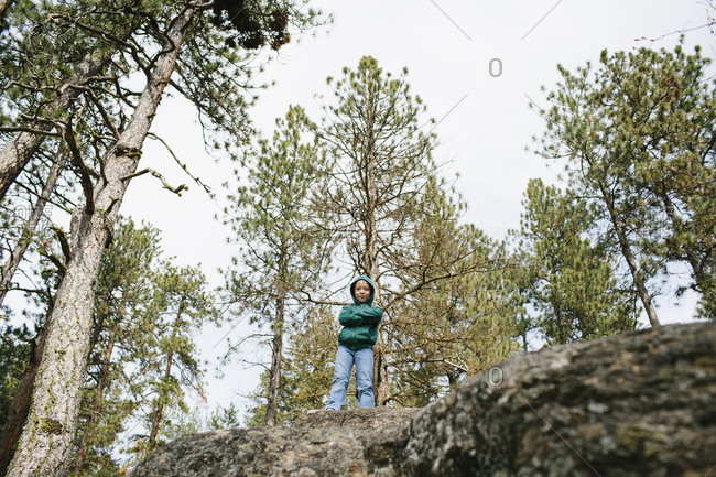 Boy crossing his arms and smiling on top of a rock in the woods