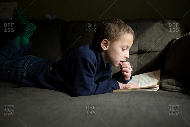 Boy lying on couch reading his book
