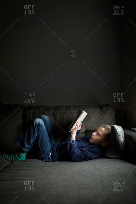 Boy lounging on couch reading his book