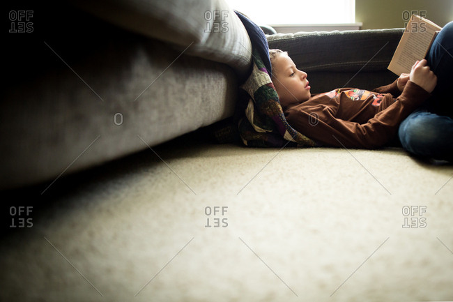 Boy lounging against couch reading  book