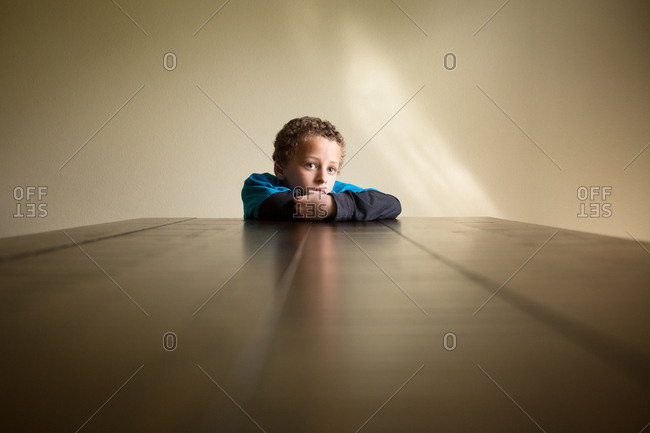 Boy at table staring quietly