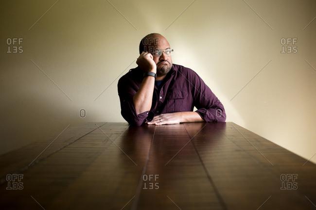 Man at table gazing away