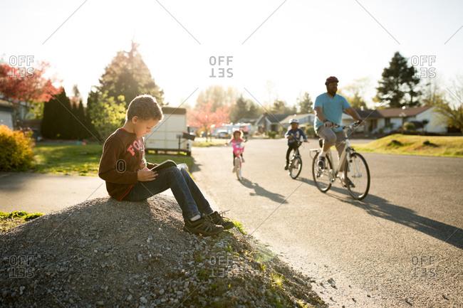 Boy reading while family bikes