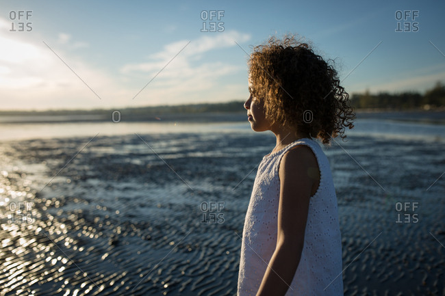 Girl staring out to sunlit ocean