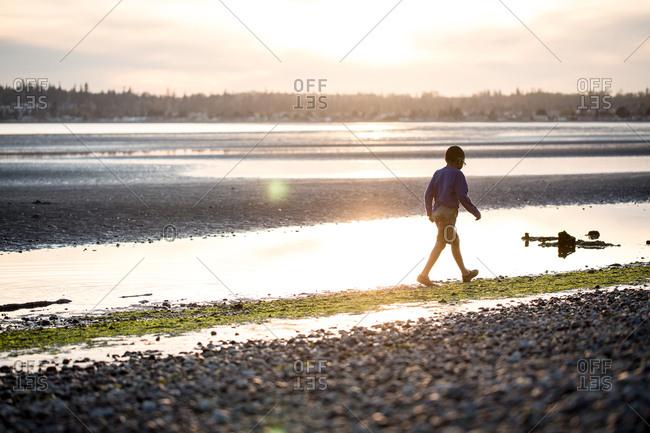 Boy walking along a sunlit coast