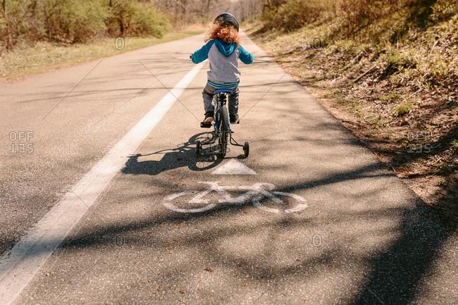 Child bike riding on a nature trail