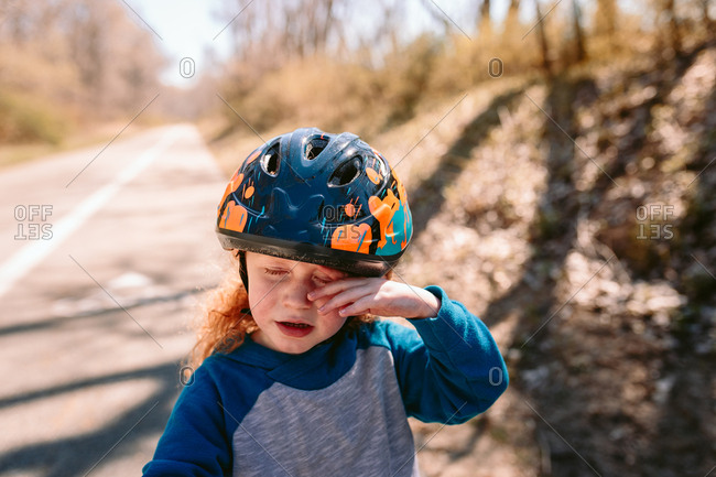 Child rubbing eye with helmet on
