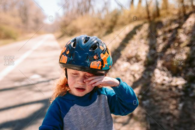 Child rubbing eye with helmet on