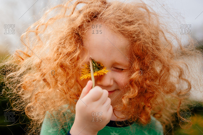 Child with dandelion covering eye