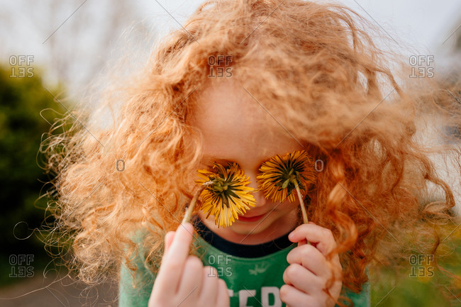 Child with dandelions covering eyes