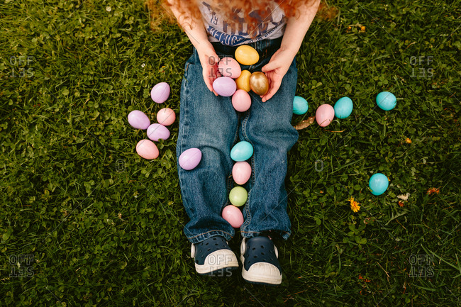 Child sitting in grass with easter eggs